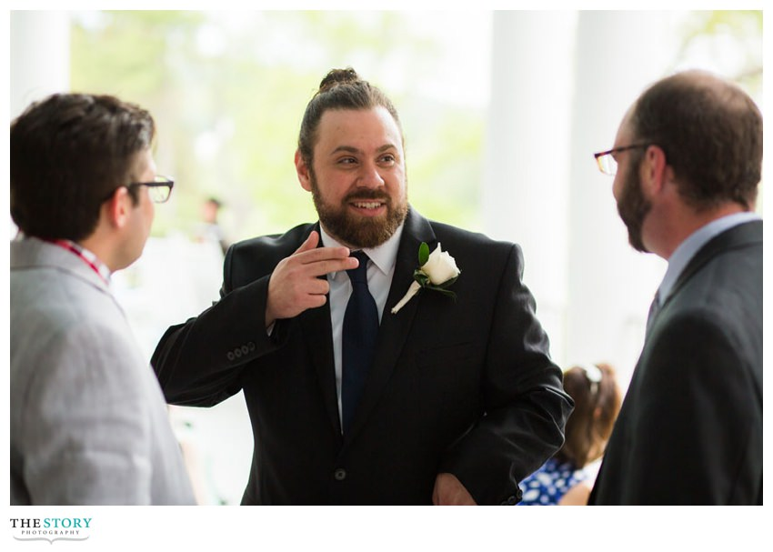 groom telling a story during the cocktail hour on the veranda at Otesaga
