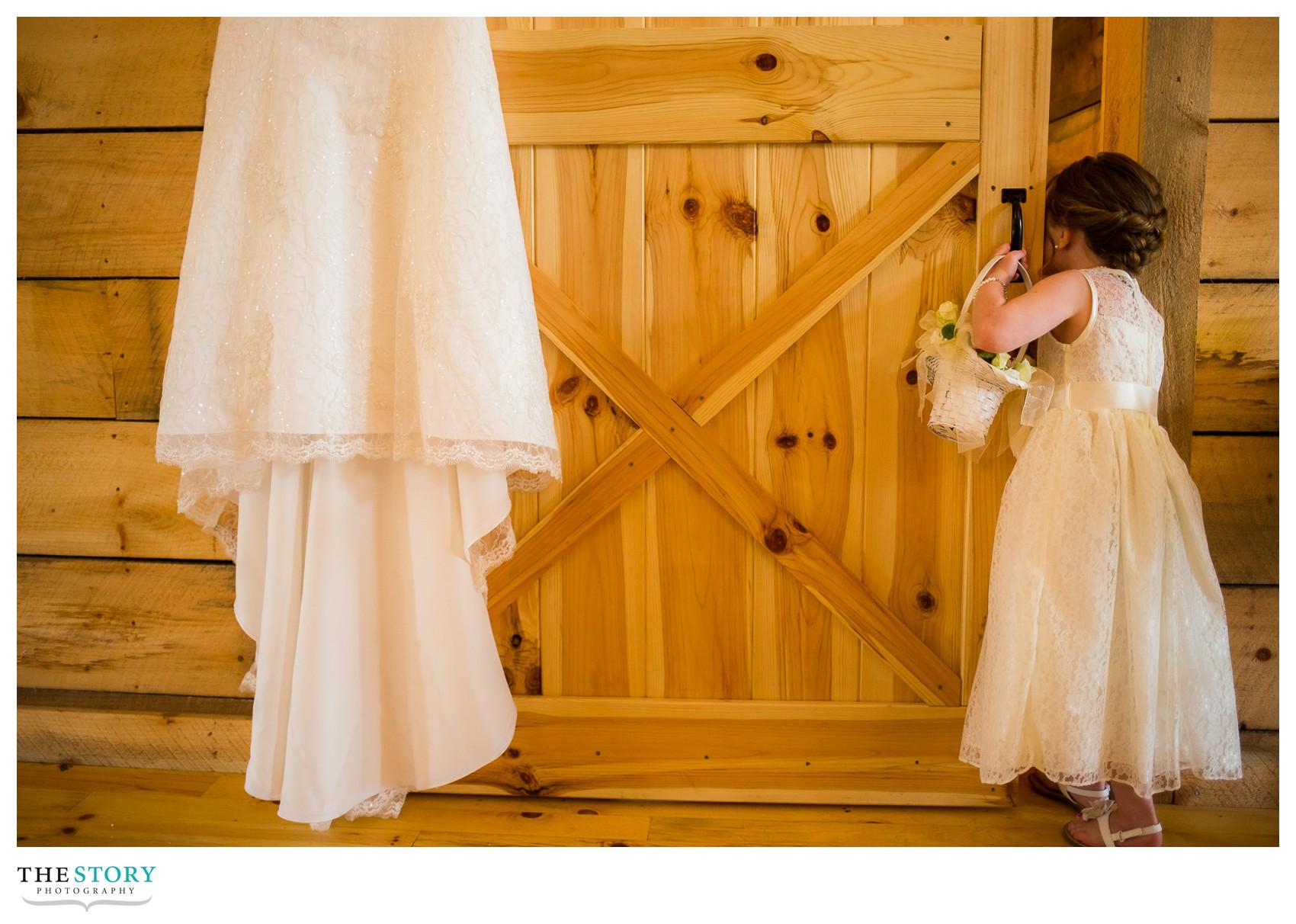 flower girl peeking in on bride getting ready for Wolf Oak Acres wedding