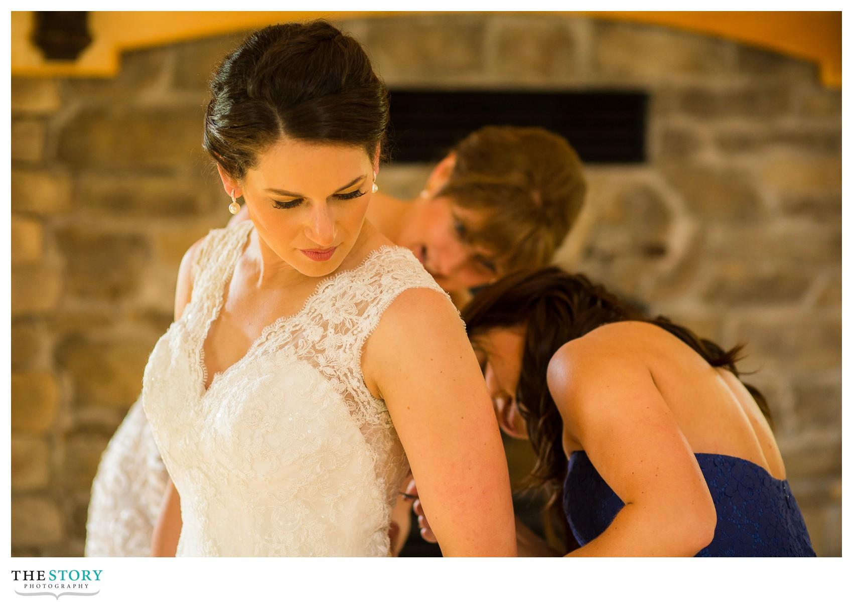 bride getting dress on in Wolf Oak Acres barn